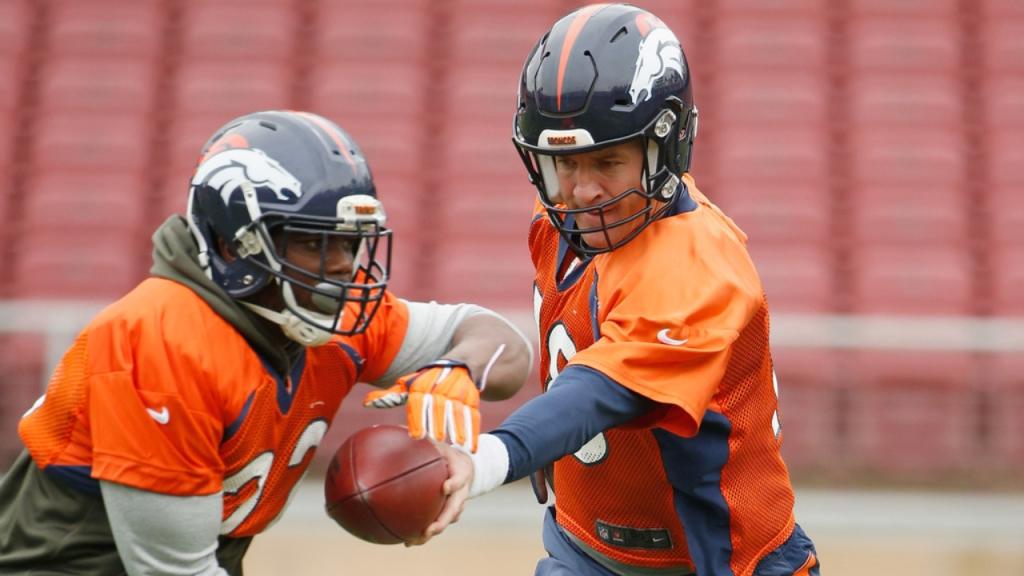 Former Denver Broncos quarterback Peyton Manning hands off to C.J. Anderson during practice before Super Bowl 50