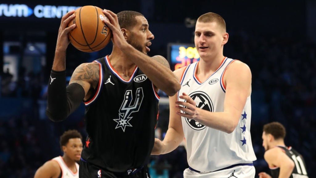 San Antonio Spurs forward LaMarcus Aldridge looks to pass the basketball while being defended by Denver Nuggets center Nikola Jokic at the 2019 NBA All-Star Game