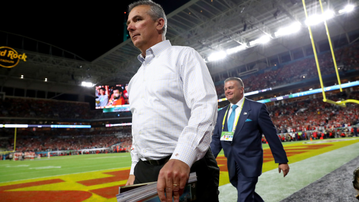 Former Ohio State Buckeyes head coach Urban Meyer walks on the field before Super Bowl LIV between the Kansas City Chiefs and the San Francisco 49ers